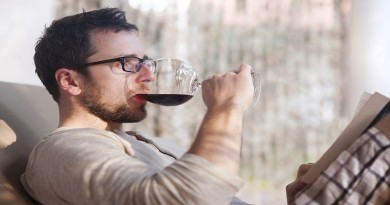 Young handsome man relaxing, reading book and drinking red wine