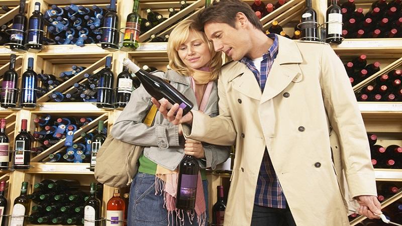 Couple choosing wine in supermarket, smiling