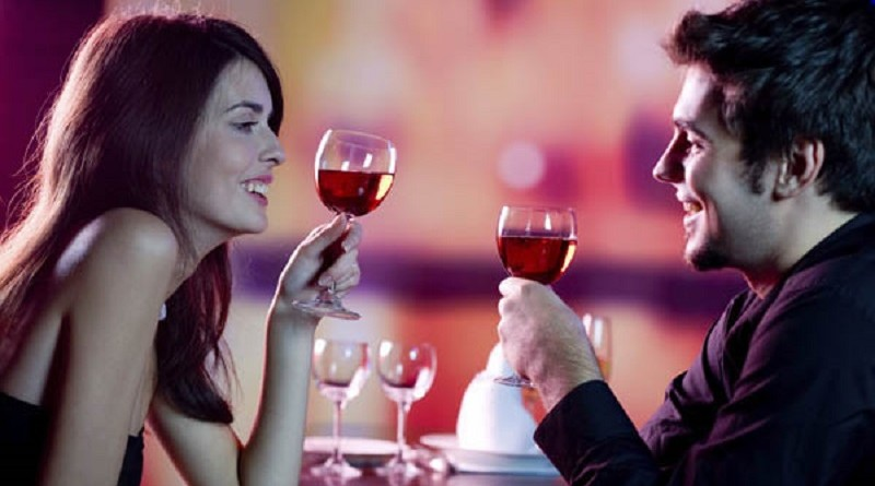 Young happy amorous couple celebrating with red wine at restaurant